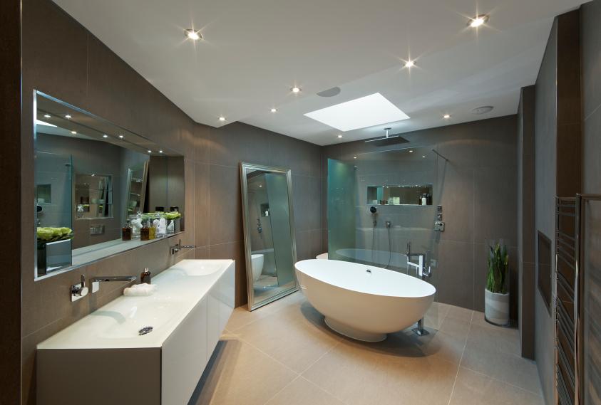 Modern-bathroom-design-in-large-travertine-floor-tiling-featured-porcelain-bathtub-and-skylight-window.jpg