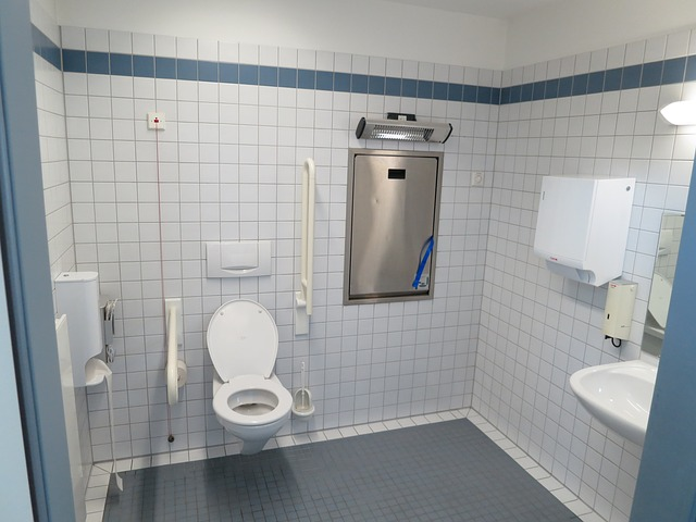 public-handicap-bathroom-with-toilet-and-undermount-sink-under-frameless-mirror-in-white-bathroom-wall-tiles.jpg